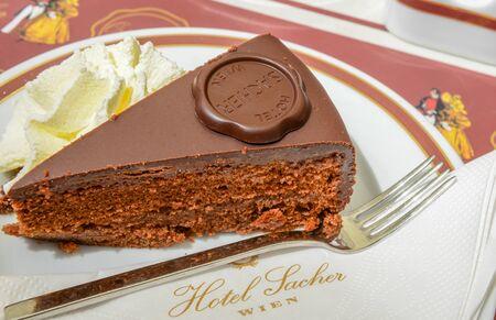 torte: VIENNA, AUSTRIA - JUNE 01. 2016: Original Sacher Torte with cream and fork at Sacher Cafe, Vienna, Austria, Europe june 01, 2016