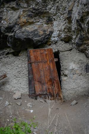 tomb empty: old wooden door in rock wall beside a street at swiss alps Stock Photo