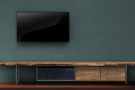 interior decoration accessories: led tv on dark green wall with media furniturein living room