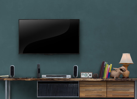 flat screen: led tv on dark green wall with media furniturein living room