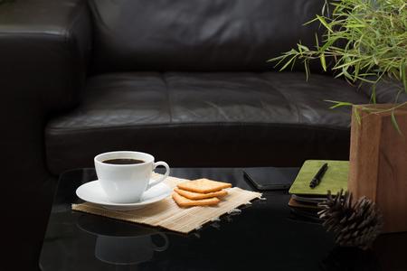 tazza di caffè bianco e biscotti sul tavolo in vetro con divano marrone scuro nel soggiorno