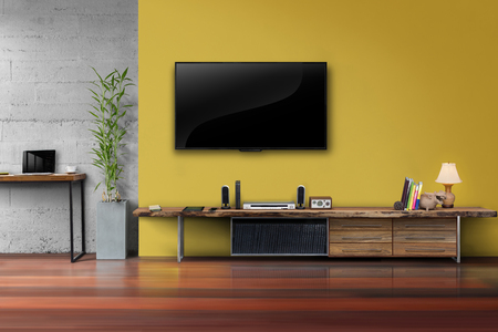 led tv on yellow wall with wooden table media furniture in living room