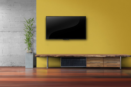 Living room led tv on yellow wall with wooden table and plant in pot modern loft style