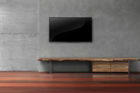 Led tv on concrete wall with wooden furniture in empty living room modern loft style modern loft style