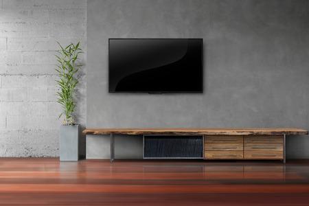Salón LED TV en la pared de hormigón con mesa de madera y una planta en estilo moderno loft olla Foto de archivo