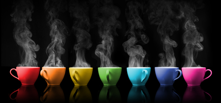 Hot drink mug the rainbows color placed on colour black background