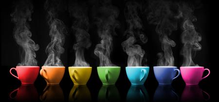 Gorący napój kubek kolor tęczowy umieszczony na kolor czarny Zdjęcie Seryjne