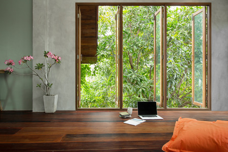 Laptop with notebook and big seat cushions on wooden floor in empty living room