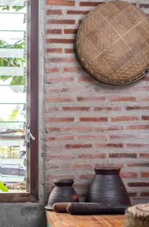 Threshing basket on brick wall in kitchen interior