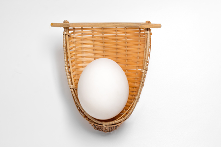 White egg in bamboo weave basket on white background 版權商用圖片