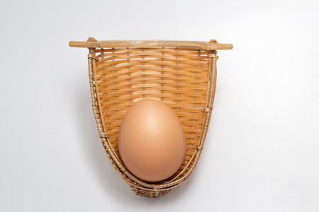 Chicken egg in bamboo weave basket on white background 版權商用圖片