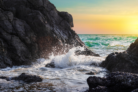 Water waves and splashes breaking on rocks in sunset of sea background 版權商用圖片