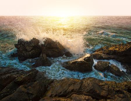amanecer: Olas de agua y salpicaduras rompiendo en las rocas en la puesta de sol de fondo de mar