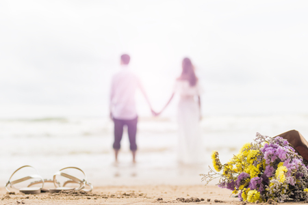 bouquet of violet and yellow flowers on beach with couple blurred bright background Reklamní fotografie - 95257200