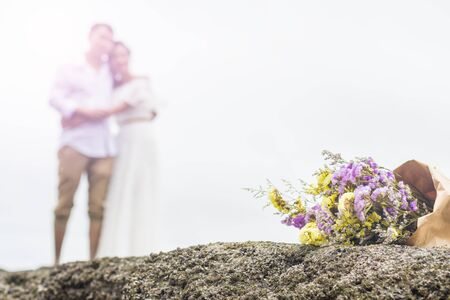 bouquet of violet and yellow flowers with couple blurred bright background