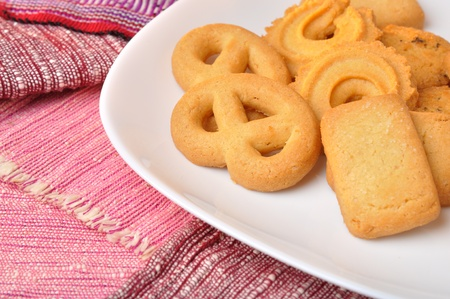 stack of fresh butter cookies in plate on pastel cloth, eating with coffee or tea