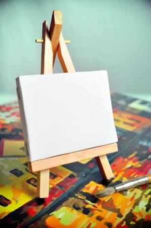 Toile vierge sur un chevalet sur un autre cadre photo avec une brosse