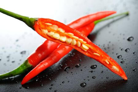 fresh red hot chili peppers on black table photo
