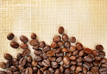 closeup roasted coffee beans scatter on sack photo