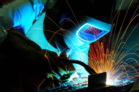 steel industry: sparks while welder uses torch to welding