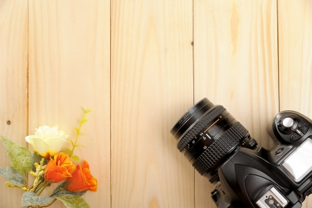 slr: wooden desktop with SLR Camera and flowers Stock Photo