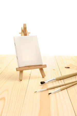 Blank canvas on easel on wooden desktop photo