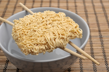 dry instant noodles over boiled water in bowl