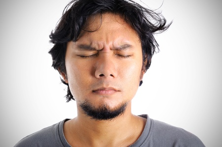 closeup asian man suffering from headache on white background photo