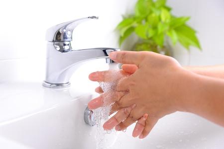 laver les mains sous l'eau du robinet qui coule dans la salle de bain