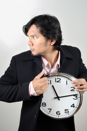 asian businessman stealing the clock in to his suit