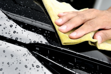 hand wiping water on black car photo