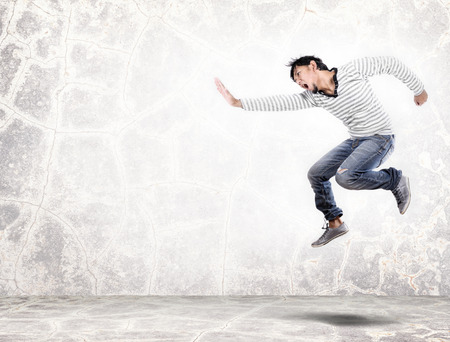 isolated handsome asian man jumping and showing the hand