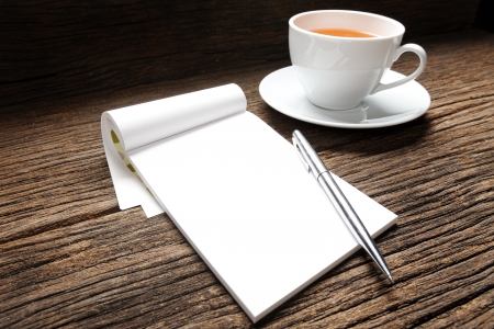 blank white notebook with cup of tea on desk photo