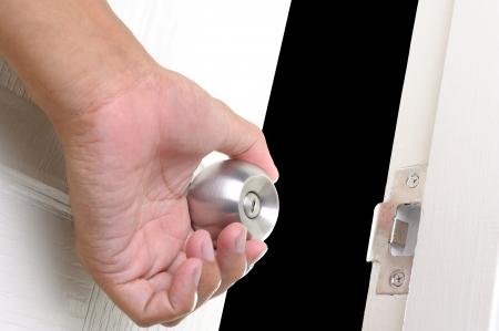 ajar: closeup human hand opening the white door Stock Photo