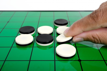 closeup discs on green Reversi board (Othello)