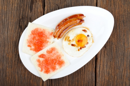 fired egg: breakfast set, fired egg, sausages and sliced of bread with strawberry jam