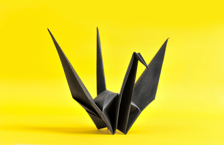The black origami bird on yellow paper photo