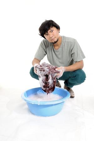 lavando ropa: Hombre tailandés lavado de las manos en un recipiente de plástico