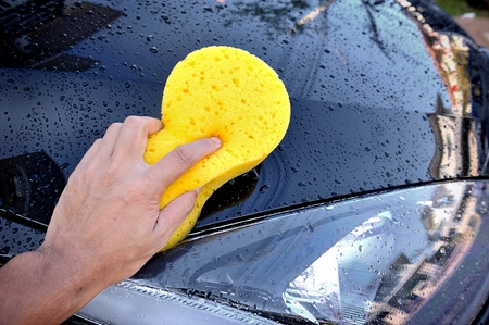 the man using yellow sponge to wash his car photo