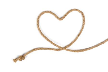흰색 배경에 고립 된 황 마 로프에 심장 모양의 매듭