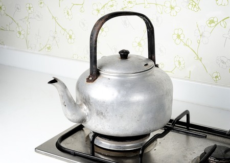 isolated old and grungy aluminium kettle photo