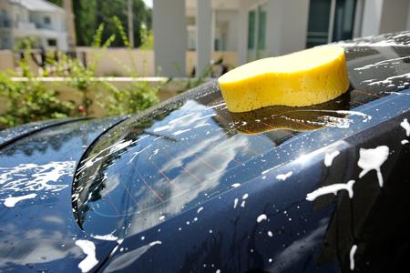 closeup yellow sponge on black car with water splash photo