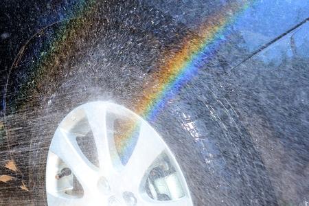 abstract water splash with rainbow during washing car wheel  photo