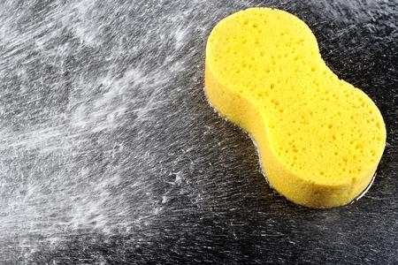 closeup yellow sponge on black car with water splash 스톡 콘텐츠