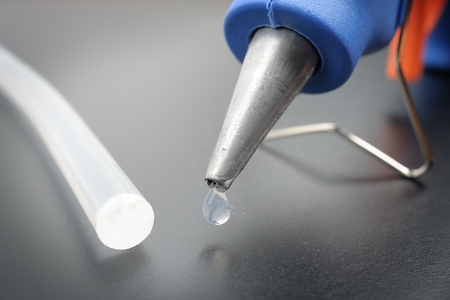 closeup hot glue gun nozzle with melted glue dripping out