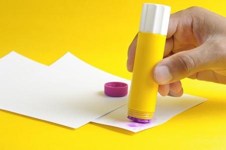 applying purple glue stick to white paper 스톡 콘텐츠