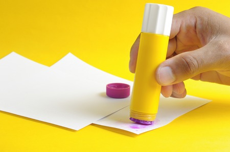 applying purple glue stick to white paper Stockfoto