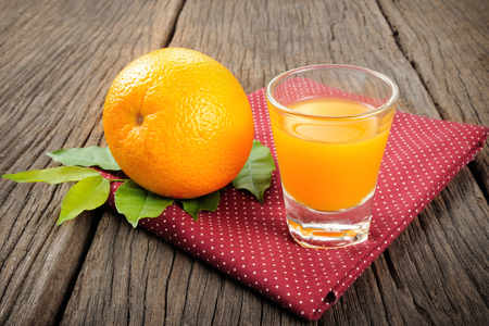 Ripe orange and cup of orange juice on wooden table photo