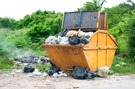 dumpster: yellow dumpster with household garbage Stock Photo