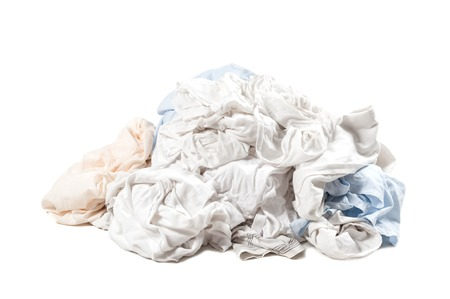 Big heap of dirty light color clothes isolated on white background